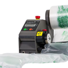 Voici une Machine de calage et protection en coussin d air qui gonfle les rouleaux de film pour en faire des coussins d'air, celle ci est légèrement plus grande qu'un ballon de basket, elle est gris foncé avec des boutons rouge et vert.