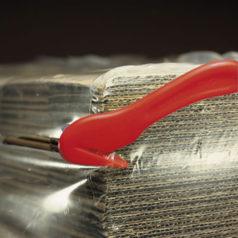 Ici vous pouvez voir des cartons emballés dans du film rétractable, le film est coupé à l'aide du couteau ou cutter pour film.